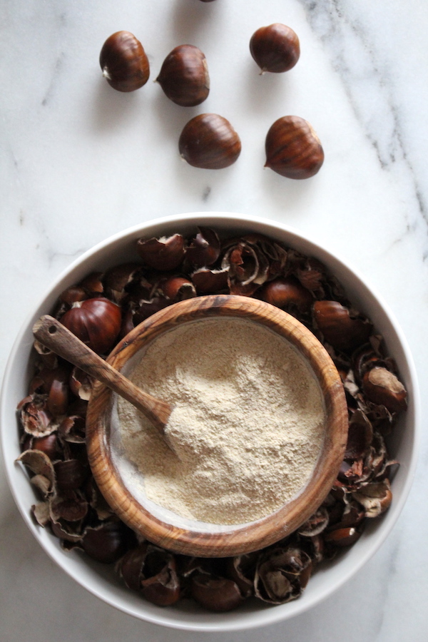 Homemade chestnut flour in a bowl amongst fresh chestnuts and chestnut shells.